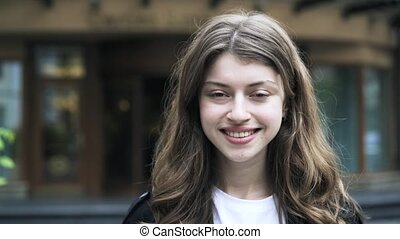 Close up of a young woman smiling and looking at you in the street
