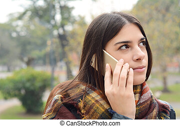 Close up of a young woman talking on the phone.