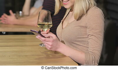 Close up of a young woman uses smartphone at the bar