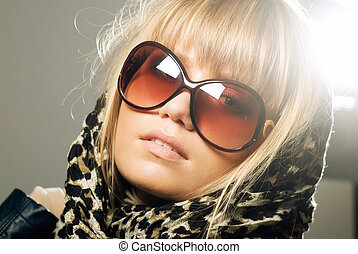 Close-up of a young woman wearing sunglasses and a scarf