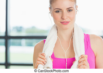 Close up of a young woman with towel around neck listening to music in fitness studio