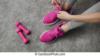 Close up of active girl tying laces on sneakers to prepare ...