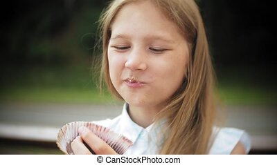 Close up of adorable little girl eating a cake with her hands sitting on a bench in the park