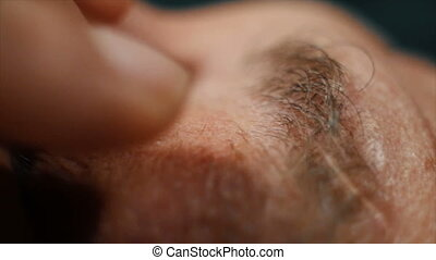 Close up of adult man rubbing his eye