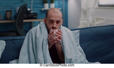 Close up of adult shivering and holding cup of tea against virus symptoms. Sick man having chills and temperature in blanket while looking at camera. Unwell person with flu and disease