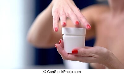 Close up of adult woman applying body lotion at home
