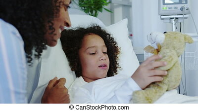 Close-up of African american mother and son playing with teddy bear in the ward at hospital 4k