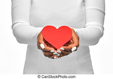 close up of african american woman with red heart