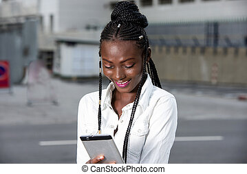 Close up of african girl with mobile phone, smiling.
