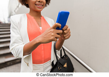 close up of african woman with smartphone in city