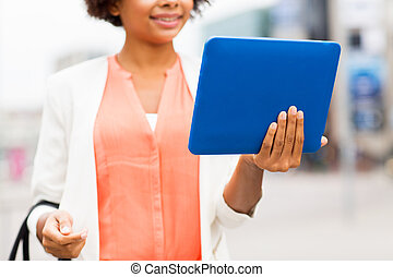 close up of african woman with tablet pc in city