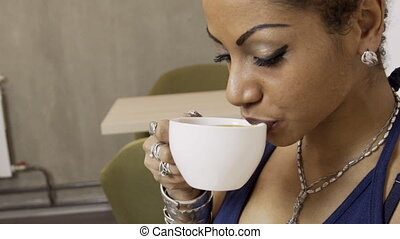 Close up of afroamerican woman who is drinking coffee in the cafe.