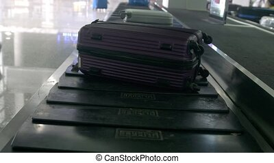 Close up of airport baggage claim with luggage spinning...