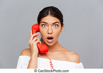 Close up of amazed woman talking on the phone tube