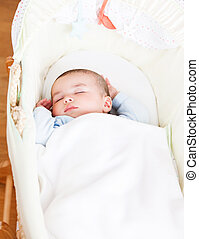 Close-up of an adorable baby sleeping in his cradle at home