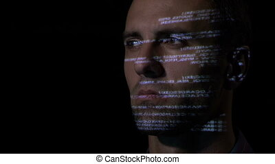 Close up of an adult male IT programmer working in a dark office room while the sequential code is reflected on his face