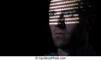Close up of an adult man with beard looking at a monitor screen while the blockchain symbol is reflected on his face