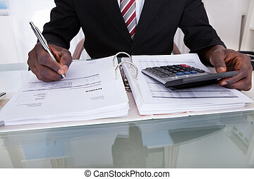 Businessman Doing Calculations - Close-up Of An African...