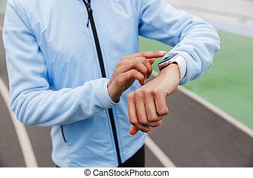 Close up of an african sportswoman using smartwatch
