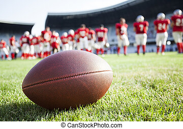 Close up of an american football on the field, players in...