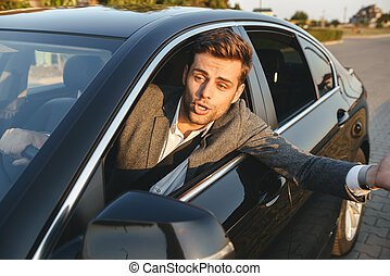 Close-up of an angry man looking outside car window