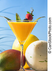 martini glass of orange juice with leaves and a skewer with a blackberry and a strawberry