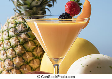 martini glass with orange juice, an apricot slice, a strawberry and a blackberry