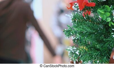 Close-up of an artificial Christmas tree, the background is out of focus, a woman tries on clothes. Shopping center