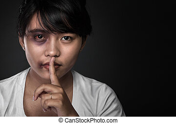 Close up of an asian girl. Holding her finger, showing to keep s