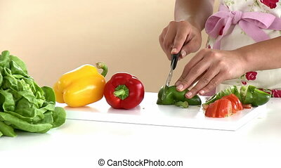 Close-up of an asian woman cutting vegetables in the kitchen...