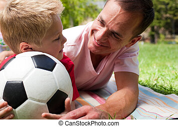 Close-up of an attentive father and his son holding a soccer ball in a park