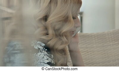 Close up of an attractive woman talking on the phone sitting in a restaurant on the summer terrace in front of laptop