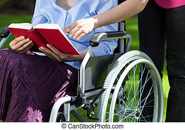 Close-up of an elderly woman in a wheelchair reading a book...