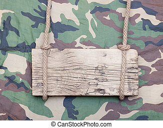 close up of an empty wooden sign hanging on a rope on military fabric