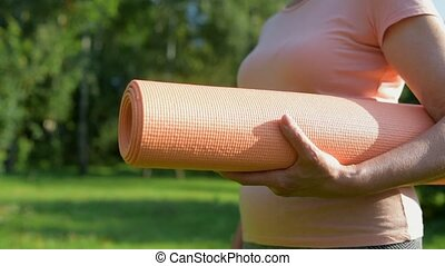 Close up of an exercise mat in hands of an aged sporty woman