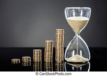 Close-up Of An Hourglass Near Stack Of Coins Over Gray Background