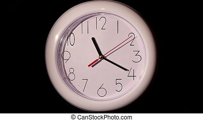 close up of an office clock on black background. slow motion