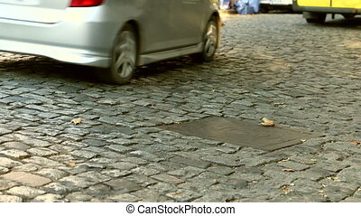 Close up of an old cobblestone road and cars passing in a...