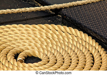 Close-up of an old frayed boat rope in circle, on the deck of a boat
