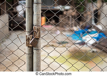 Close up of an old lock and a rusty chain on an iron gate