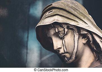 close up of an old sculpture of a sad woman