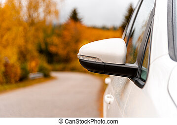 Close-up of an outside mirror of a white vehicle or car - concept of transportation, autumn holiday or autumn vacation and roadtrip - in the background you can see a colorful autumn forest