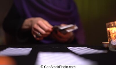 Close-up of an unidentified slim young woman with black nails and a ring lays cards on a black table in dark lighting and a burning candle. Concept of sin and in connection with the dark forces