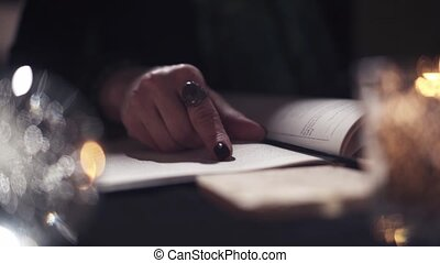 Close-up of an unknown female witch mage casting a spell in a magic book to plot for her client. The concept of conspiracies and love spells. Black magic concept