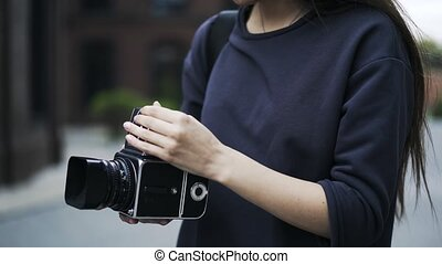 Close up of an unrecognizable girl with an old fashioned camera outside