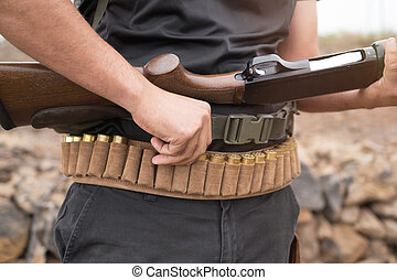 Close up of an unrecognizable hunter, loading shotgun, holds a shotgun and ammunition in his hand.