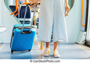 Close up of an unrecognizable woman carrying a suitcase, traveling by train.