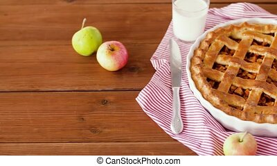 close up of apple pie and glass of milk on table