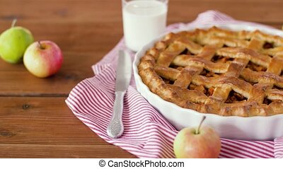 close up of apple pie and glass of milk on table - food,...