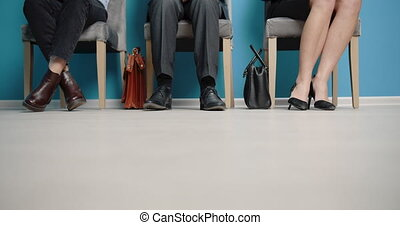Close up of applicants legs waiting for job interview - ...